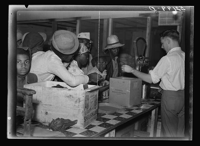 Black day-laborers await their pitiful payment at a plantation in 1940s Mississippi (Library of Congress)